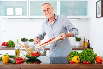 Mature man in the kitchen prepare salad II
