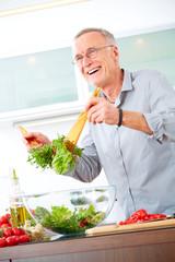 Mature man in the kitchen prepare salad