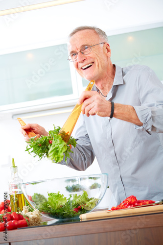 Mature man in the kitchen prepare salad - 79512674