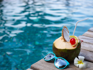 Coconut cocktail with drinking straw by the swimming pool