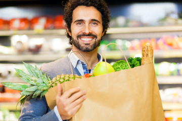 Smiling man shopping in a supermarket