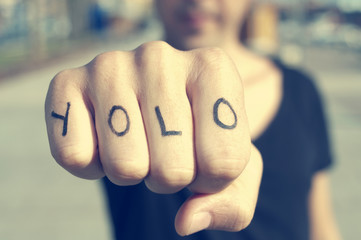 young man with the word yolo, for you only live once, tattooed i