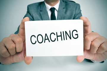 man with a signboard with the word coaching