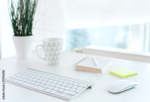 Office table with notepad, computer, flower and coffee cup - 79516418