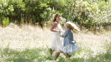 Mother and daughter playing holding hands and spinning outdoors