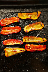 Composition with roasted sliced pepper on pan, close-up