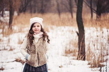 winter portrait of adorable child girl in snowy forest