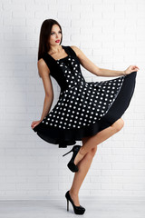 Young woman in black dots dress