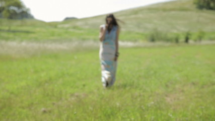 Young woman walking in nature with wind blowing her hair