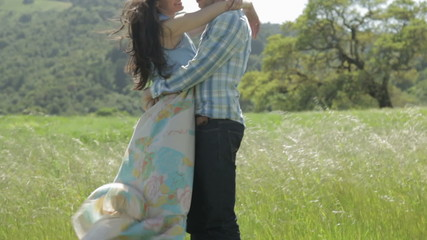 Young couple hugging each other outdoors in nature
