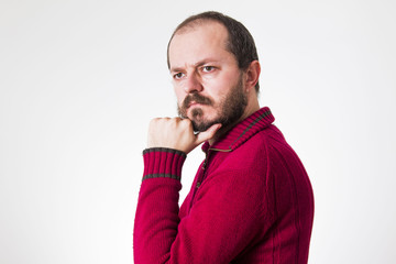 Man in red sweater, with beard and mustaches in skeptic pose