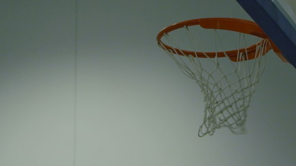 Basketball passing through the hoop in slow motion
