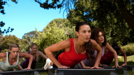 In high quality format fitness group using steps in park