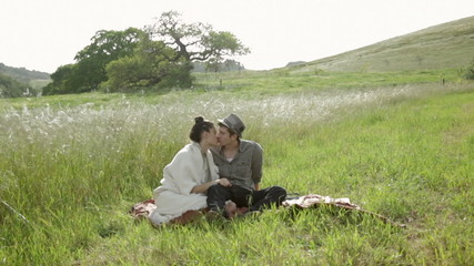 Young couple sitting on a blanket and kissing in nature