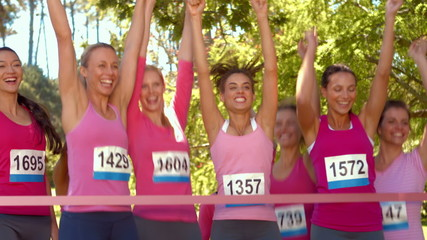 Smiling women running for breast cancer