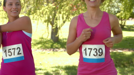 Smiling women running for breast cancer awarness