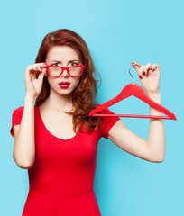 Surprised redhead girl with hanger