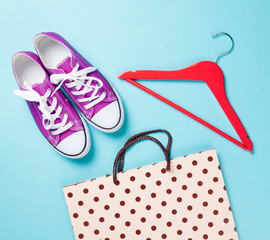 gumshoes with white shoelaces and hanger with shopping bag