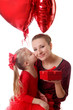 Girl kissing mother and giving gift box with balloons