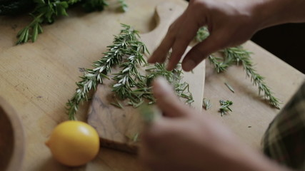 Man peeling the leaves off rosemary stem in kitchen
