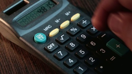 Male businessman hand pushing key on a calculator, the digits