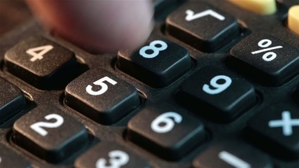 Male businessman hand pushing calc buttons. Calculates income