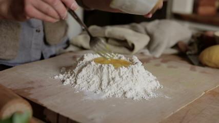 Woman pouring beaten eggs on flour while making pasta