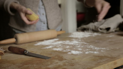 Woman sprinkling flour on a cutting board while making pasta
