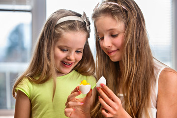 Children paint Easter eggs at home
