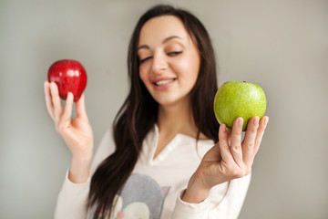 Young woman holds two apples and smiling