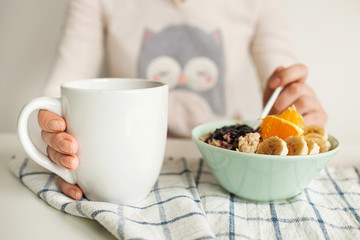 Woman holds tea cup and spoon with porridge and fruits