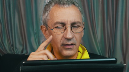 Portrait Smiling Man in Glasses Reading a Tablet Computer,
