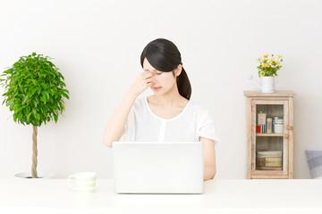 パソコンの前で目頭を押さえる女性