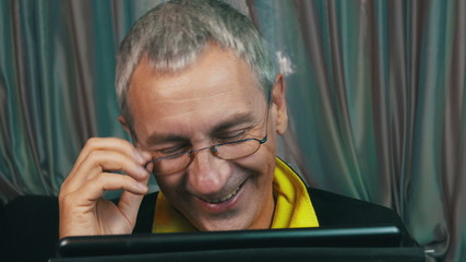 Portrait Laughing Man in Glasses Reading a Tablet Computer