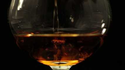 In a glass pour brandy, black background