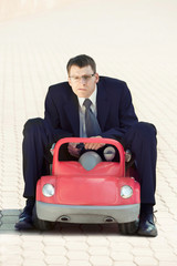 Disappointed Businessman Sitting in the Red Toy Car