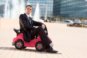 Big Businessman Sitting in the the Little Red Toy Car
