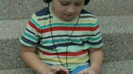 4 years old boy listening to music on phone