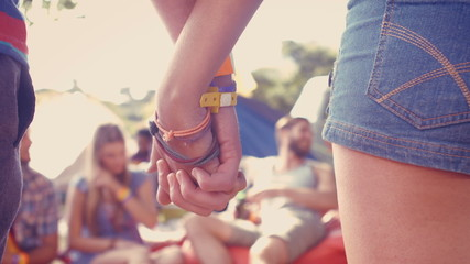 In high quality format hipster couple holding hands on campsite