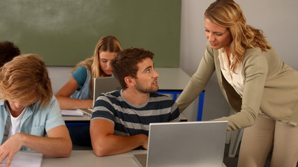 Teacher helping student with laptop