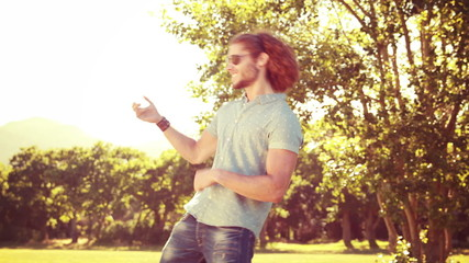 Young man playing air guitar in the park
