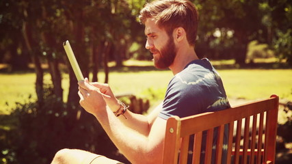 In high quality 4k format young man using tablet on park bench