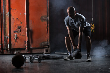 Bald charismatic athlete doing squats with weights.