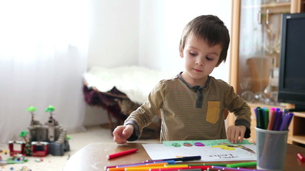 Adorable little boy, drawing picture for easter