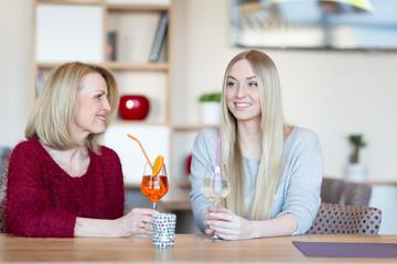 Mutter und Tochter trinken Weißwein im Restaurant
