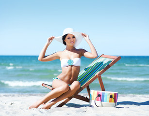 Young, beautiful and sexy woman relaxing on a summer beach
