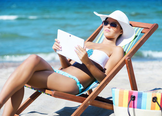 A young woman relaxing with a tablet computer on the beach