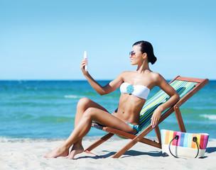 Sexy woman with a sun protection cream on a summer beach