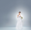 Young and beautiful bride in a long fantasy dress standing with