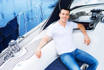 A handsome man relaxing on a boat on the sea